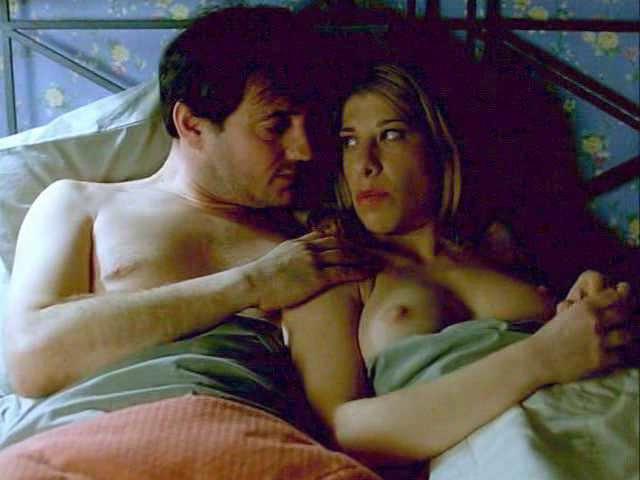 En la cama enseñando los pechos